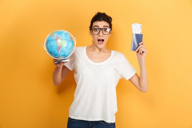 Возбужденная удивленная женщина в очках держит глобус и паспорт с билетами.