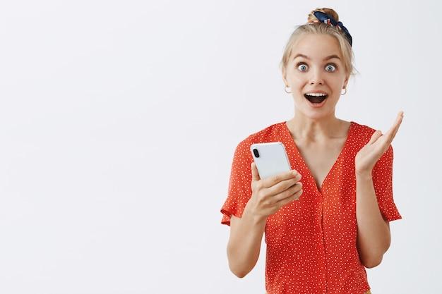Giovane ragazza bionda emozionante e sorpresa che posa contro il muro bianco