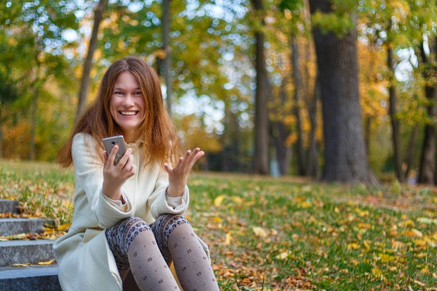 Excited surprised young caucasian woman with phone on the stairs outdoors