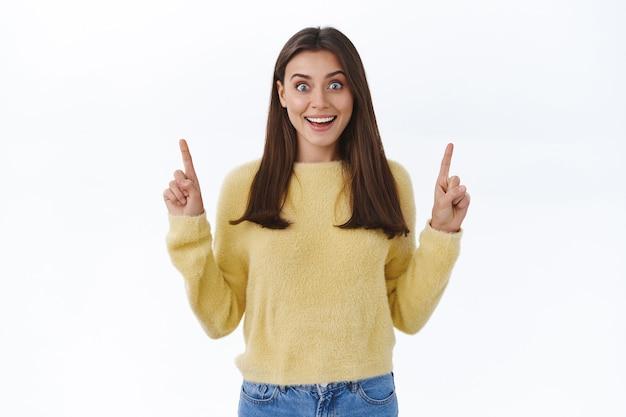 Una giovane donna eccitata e sorpresa ha trovato qualcosa di incredibile, puntando le dita in alto e guardando la telecamera stupita con un sorriso elettrizzato che raccontava a tutti di eventi interessanti o offerte promozionali, muro bianco