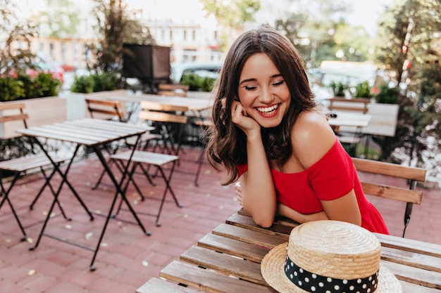 Excited tanned girl looking at her straw hat. outdoor portrait of debonair laughing woman posing in street cafe.