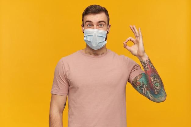 노란색 벽에 수염이 서서 확인 표시를 보여주는 코로나 바이러스에 대한 얼굴에 분홍색 티셔츠와 바이러스 보호 마스크에 문신을 한 젊은 남자가 흥분했습니다.