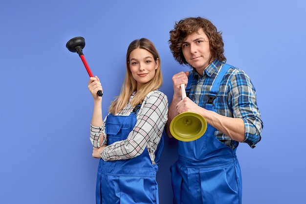 Excited team of two plumbers dressed in blue uniform with plunger, being glad to repair bathtub