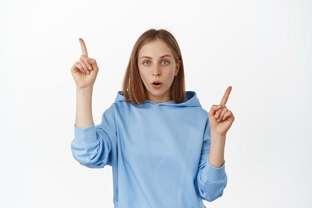 흥분한 10대 여성은 판매 광고에 대해 이야기하고, 손가락을 옆으로 가리키고, 두 개의 프로모션 텍스트, 할인 배너를 보여주고, 앞, 흰 벽에 깊은 인상을 받았습니다.