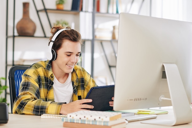 컴퓨터에서 숙제를하는 대신 태블릿 컴퓨터에서 tv 시리즈를 시청하는 헤드폰에 흥분된 십 대 소년