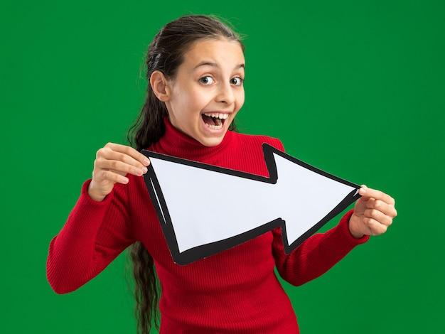 녹색 벽에 고립 된 카메라를보고 측면을 가리키는 화살표 표시를 들고 흥분된 십 대 소녀