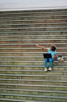 Возбужденная девочка-подросток указывая рукой, сидя на ступеньках с ноутбуком