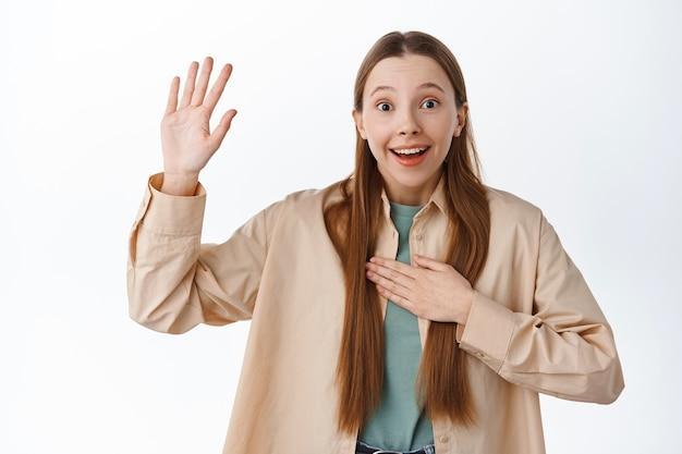 興奮した10代の少女が手を挙げて心を動かし、ボランティアをし、参加を求め、ジェスチャーを選んで、イベントに参加したい、白い壁に陽気に立っている