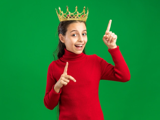 Excited teenage girl wearing crown  pointing up isolated on green wall with copy space