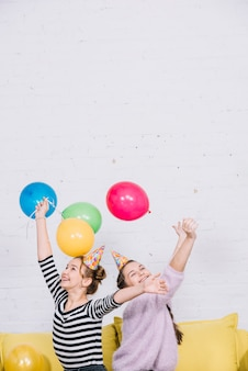 Excited teenage girls raising their hands holding colorful balloons