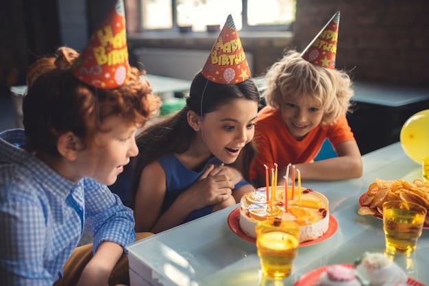 興奮しました。 3人の子供がケーキを見て興奮している