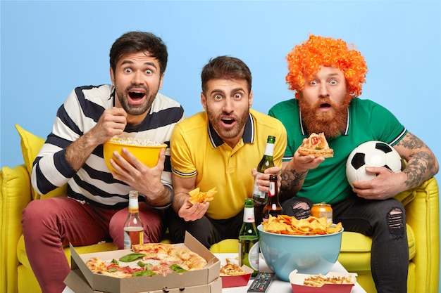 Excited three male friends concentrated at screen of tv set, watch football match with great interest, pose on sofa in spacious living room, eat popcorn