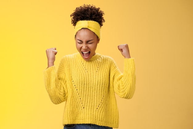 Excited thrilled beautiful young girl student yelling happily clench fists victory triumph pose dancing celebrating acception popular university standing satisfied achieve goal dream come true.