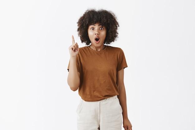 Ragazza dalla pelle scura artistica creativa eccitata ed elettrizzata con acconciatura afro che suggerisce di alzare il dito indice nella posa di eureka, piegare le labbra e ansimare raccontando la sua idea o pianificando di collaborare