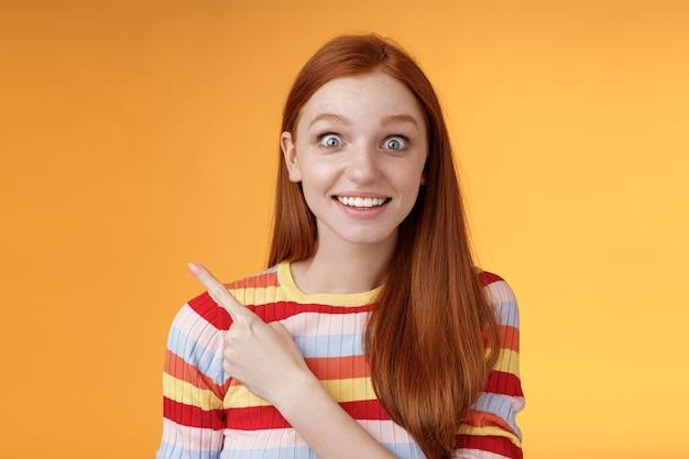 興奮したスリル満点の見栄えの良い若い愚かな赤毛の女の子は、ポップアイカメラのあえぎ感動した左上隅を指して、スーパースターのニヤリと興奮の喜び、オレンジ色の背景を見て驚いた。コピースペース