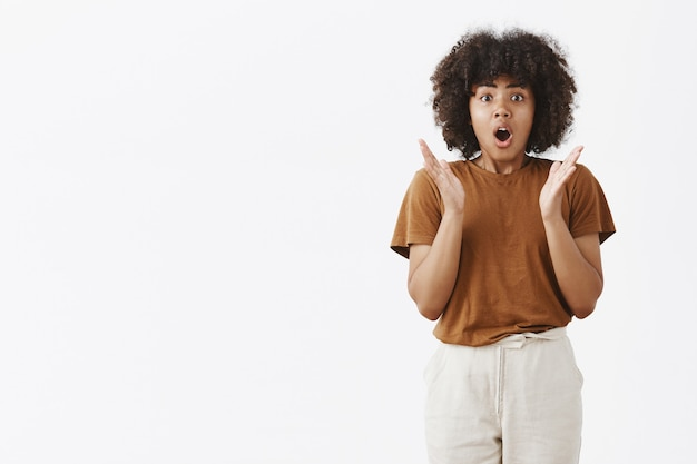 Excited and thrilled speechless african american young girl with curly hairstyle gesturing with palms near chest opening mouth and retelling with passion what happened gasping being amazed