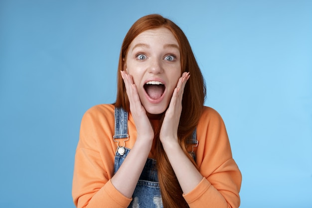 Excited thrilled young emotional enthusiasitc ginger girl teenage college student yelling amused smiling broadly receive positive good news look surprised camera touch face astonished blue background