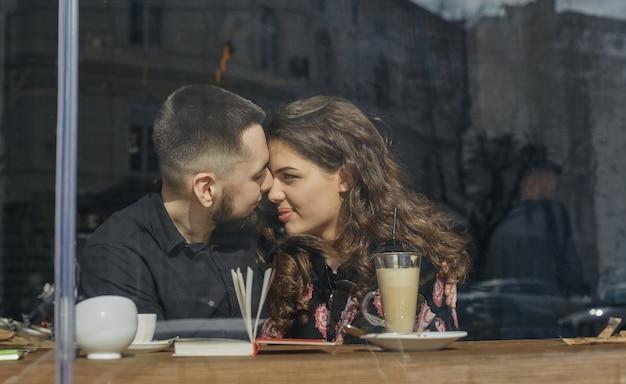 一緒にいることに興奮しています。素敵な若いカップルが通りのカフェに座っています