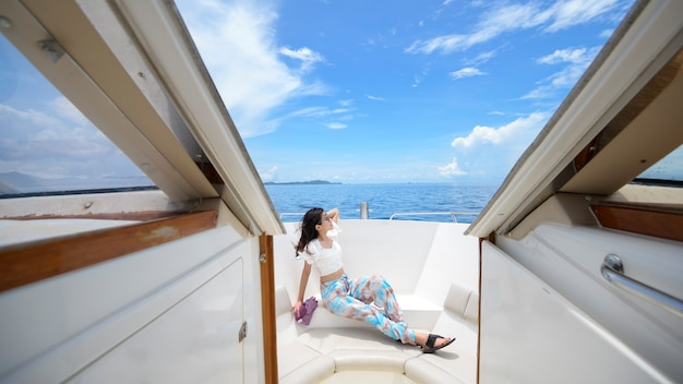 Excited tourist enjoying and relaxing on speedboat with a beautiful view of ocean and mountain