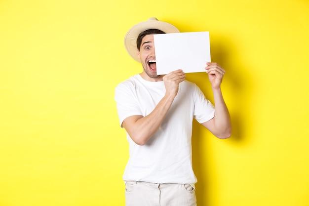 Взволнованный турист в отпуске показывает чистый лист бумаги для вашего логотипа, держит знак возле лица и улыбается, стоя на желтом фоне