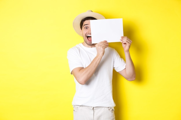 Excited tourist on vacation showing blank piece of paper for your logo, holding sign near face and smiling, standing against yellow wall