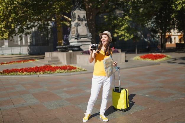 Взволнованная туристическая женщина путешественника в шляпе с картой города чемодана фотографирует на ретро старинную фотокамеру в городе на открытом воздухе. девушка едет за границу, чтобы поехать на выходные. туризм путешествие образ жизни.