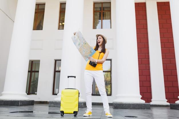 黄色の夏のカジュアルな服とスーツケースで街の屋外の都市地図を見て興奮している旅行者の観光客の女性。週末の休暇で旅行するために海外旅行する女の子。観光の旅のライフスタイル。