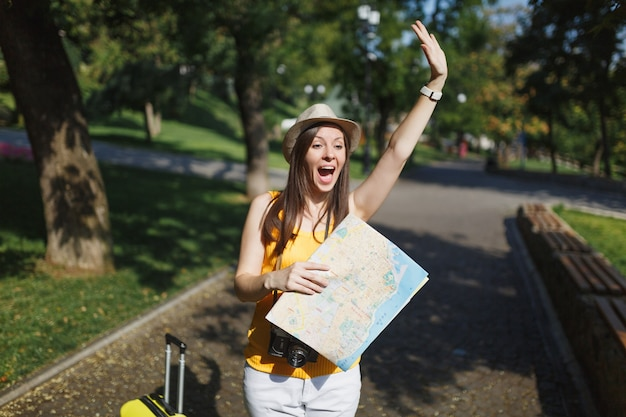 Excited traveler tourist woman with suitcase city map waving hand for greeting, meet friend, catch taxi in city outdoor. girl traveling abroad to travel on weekends getaway. tourism journey lifestyle.
