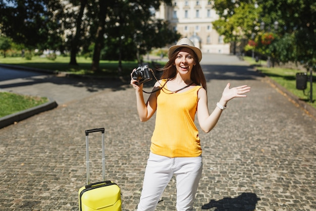 Excited traveler tourist woman in yellow casual clothes, hat with suitcase hold retro vintage photo camera spreading hands outdoor. girl traveling abroad on weekend getaway. tourism journey lifestyle.