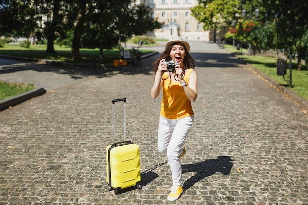 Excited traveler tourist woman in yellow casual clothes with suitcase take pictures on retro vintage photo camera running outdoor. girl traveling abroad on weekend getaway. tourism journey lifestyle.