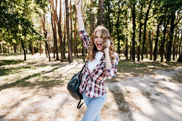 Excited trendy girl having fun on forest. blithesome female model expressing positive emotions during travel.