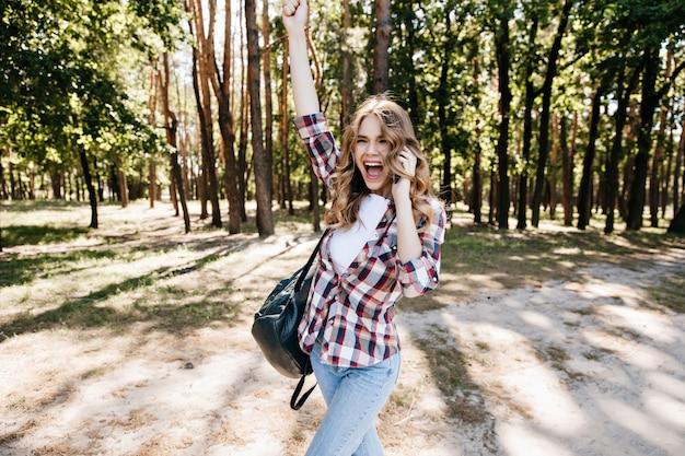 森で楽しんでいる興奮したトレンディな女の子。旅行中に前向きな感情を表現する軽快な女性モデル。