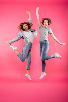 Excited two ladies friends jumping isolated