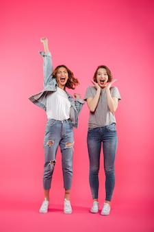 Excited two ladies friends standing isolated