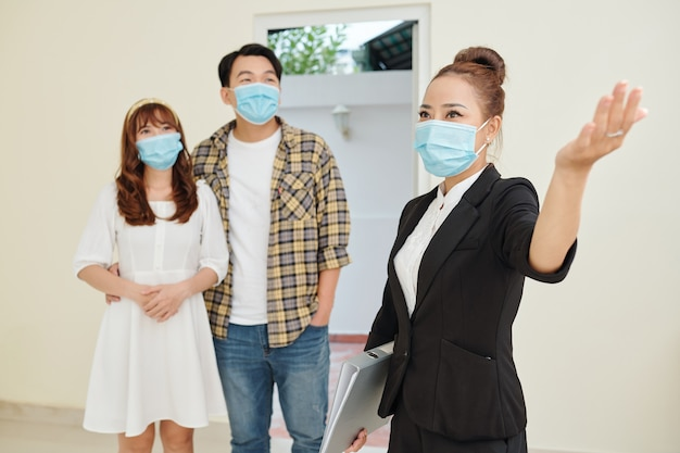 Excited vietnamese real estate agent showing rooms in big house to young couple