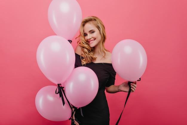 パーティーで楽しんでいる華やかなドレスを着た興奮した白人女性。幸せを表現するウェーブのかかった髪型ののんきな誕生日の女の子。