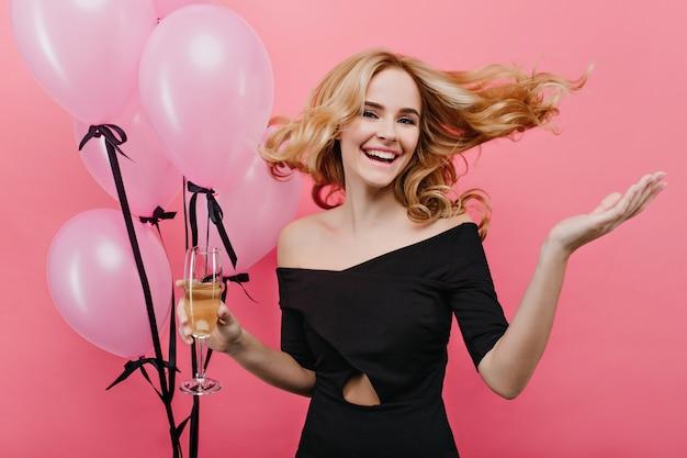 一个兴奋的白人女人在她生日那天跳到粉红色的墙上。可爱的金发女孩拿着派对气球摆造型。