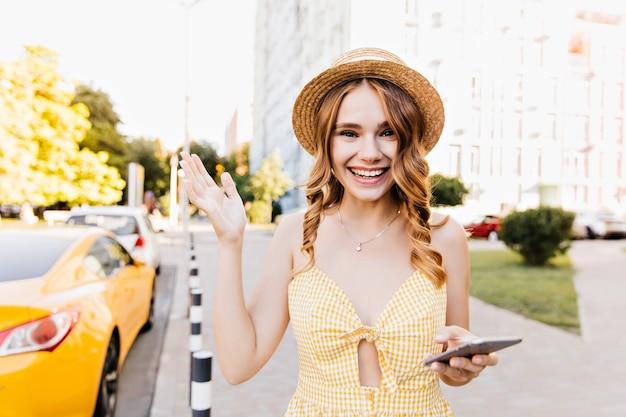 朝の路上でポーズをとって手を振る興奮した白人女性。夏の日に黄色のドレスを着ている巻き毛のブロンドの女の子。
