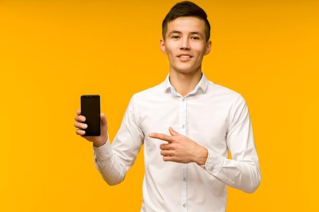 スタジオで黄色の背景に分離された良いニュースを受け取った後、携帯電話を指している興奮した勝者のアジア人男性。 -画像