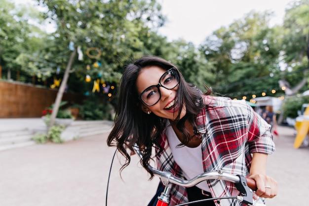 公園の周りに乗っている興奮した魅力的な女性。自然の中で自転車でポーズをとってメガネで笑っているブルネットの少女の屋外写真。