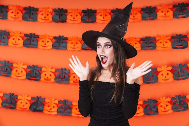Excited witch girl in black halloween costume screaming in surprise isolated over orange pumpkin wall