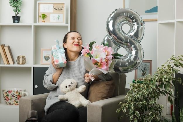 Eccitato con gli occhi chiusi bella ragazza il giorno delle donne felici che tiene presente con bouquet seduto sulla poltrona in soggiorno