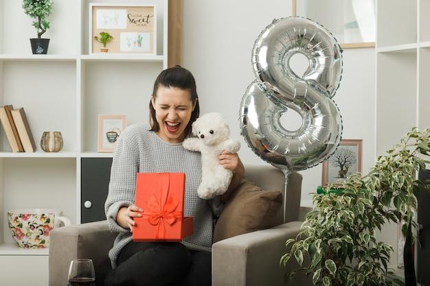 リビングルームの肘掛け椅子に座っているテディベアとプレゼントを保持している幸せな女性の日に目を閉じて美しい女性に興奮