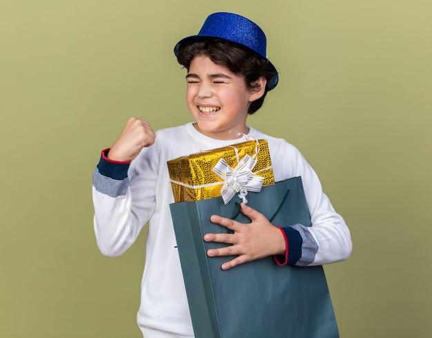 Eccitato con gli occhi chiusi ragazzino che indossa un cappello da festa blu che tiene in mano una borsa regalo che mostra un gesto di sì