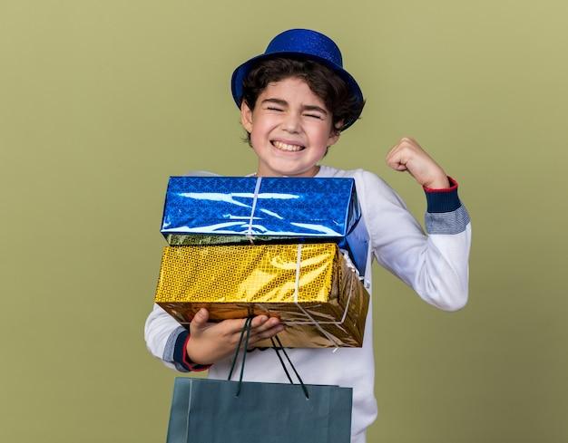 Взволнованный, с закрытыми глазами маленький мальчик в синей шляпе для вечеринок, держащий подарочные коробки с сумкой, показывающий жест да, изолированный на оливково-зеленой стене