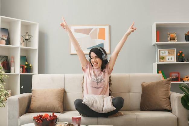 目を閉じて興奮して、リビングルームのコーヒーテーブルの後ろのソファに座っているヘッドフォンを身に着けている若い女の子を指しています