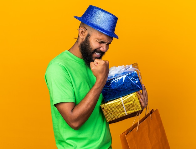 Excited with closed eyes young afro-american guy wearing party hat holding gift boxes with bag showing yes gesture isolated on orange wall