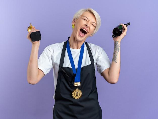 파란색 벽에 고립 된 헤어 클리퍼와 스프레이 병을 들고 메달을 입고 제복을 입은 눈을 감은 젊은 아름다운 여성 이발사 흥분