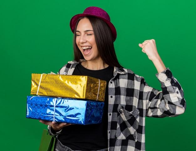 Взволнованная с закрытыми глазами молодая красивая девушка в шляпе для вечеринок, держащая подарочные коробки с подарочным пакетом, показывая жест да, изолированный на зеленой стене
