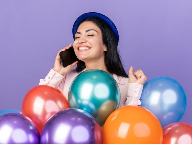 풍선 뒤에 서 있는 파티 모자를 쓴 아름다운 소녀가 파란 벽에 격리된 예 제스처를 보여주는 전화로 말합니다.